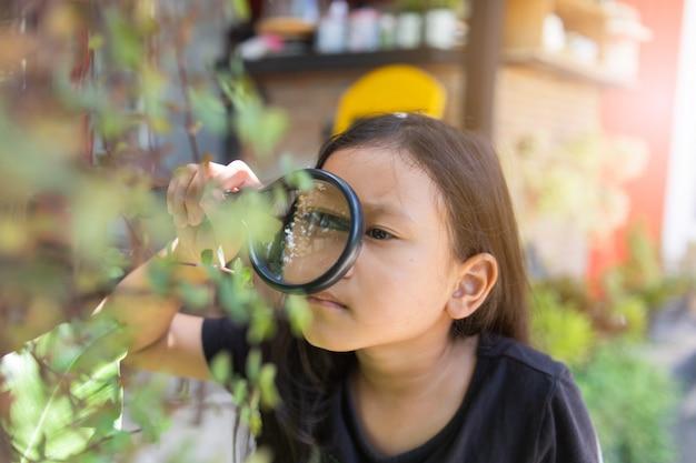 Niña asiática mirando a través de una lupa Foto Premium