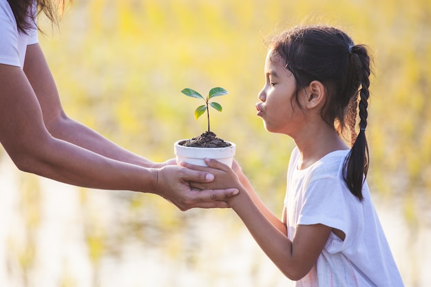 Niña asiática y su madre con plántulas jóvenes en la maceta para preparar la siembra en el suelo Foto Premium