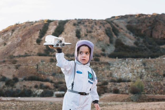 Niña astronauta jugando en la naturaleza Foto gratis