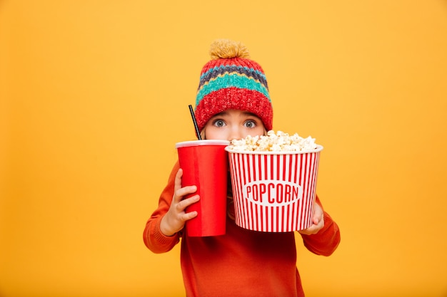 Niña asustada en suéter y sombrero escondiéndose detrás de las palomitas de maíz y un vaso de plástico mientras mira a la cámara sobre naranja Foto gratis