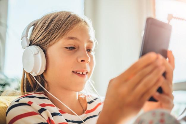 Niña con auriculares con teléfono inteligente Foto Premium