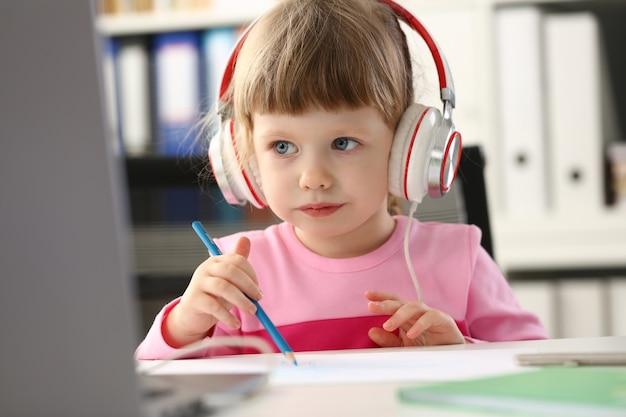 Niña con auriculares usar computadora móvil Foto Premium