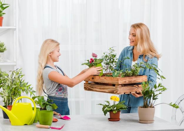 Niña ayudando a mamá a cuidar flores Foto gratis