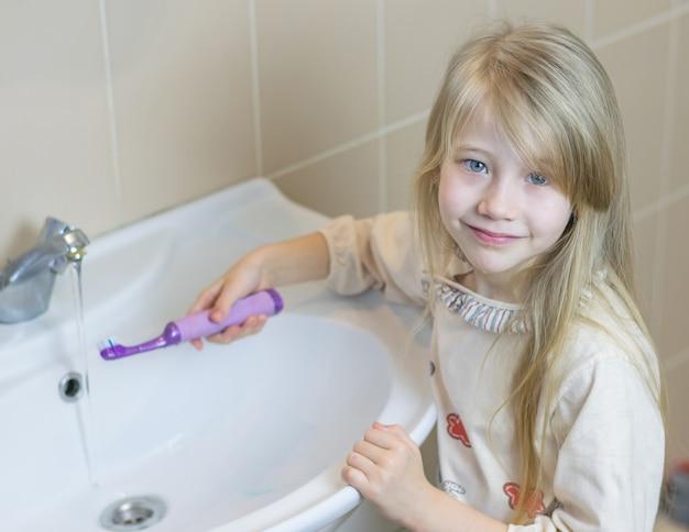 Una niña en el baño lava un cepillo de dientes eléctrico. Foto Premium