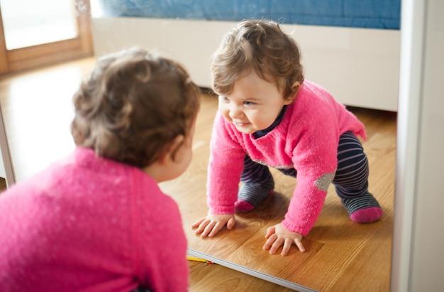 Niña bebé jugando con espejo en el dormitorio Foto Premium
