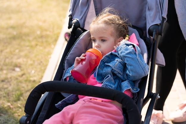 La niña bebe jugo de una botella mientras está sentada en un cochecito de bebé caminando Foto Premium
