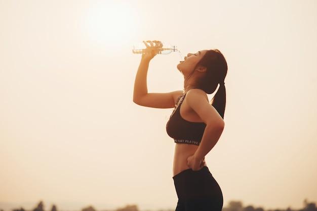 Niña bebiendo agua durante el trote Foto gratis