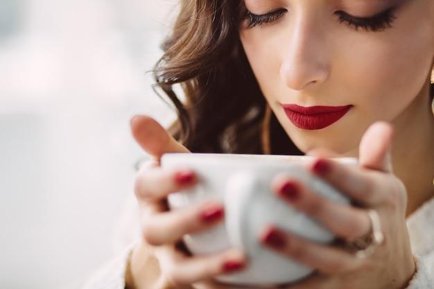 Niña bebiendo café en una cafetería de moda Foto gratis