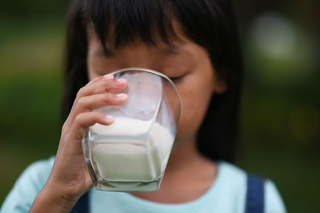 Niña bebiendo leche en el parque Foto gratis