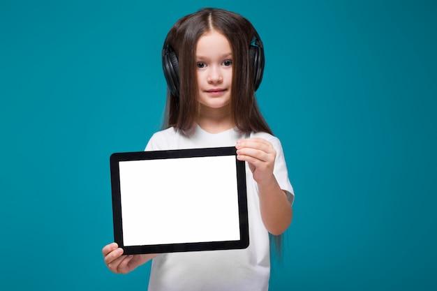 Niña de belleza en camiseta y auriculares con tableta de retención de pelo largo Foto Premium