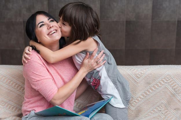 Niña, besar, madre, con, libro, en, mejilla Foto gratis