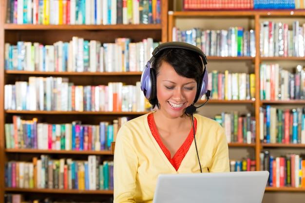 Niña en biblioteca con laptop y auriculares Foto Premium