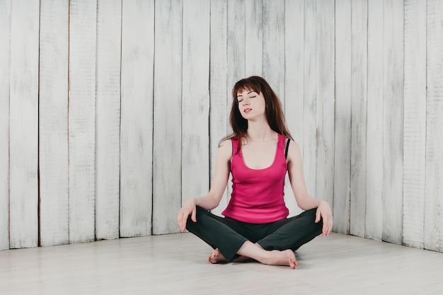 Una niña en una blusa rosa, sentada con las piernas cruzadas en el suelo, sonriendo, fondo claro Foto Premium