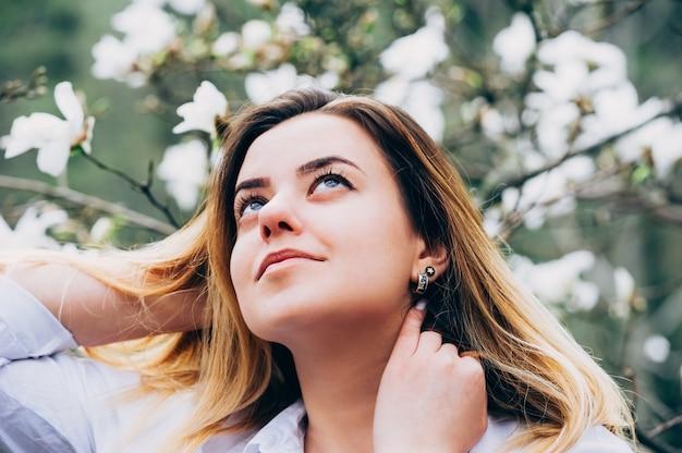 Una niña bonita en un jardín disfruta de florecientes árboles de magnolia Foto Premium