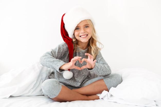 Niña bonita con sombrero de santa que muestra el signo del corazón mientras está sentado con las piernas cruzadas en la cama blanca Foto gratis