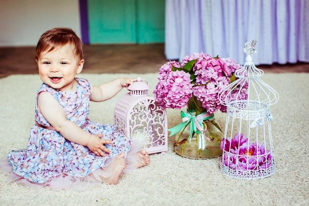Niña bonita en vestido con flores se sienta ante la linterna de color rosa y ramo de lilas Foto gratis