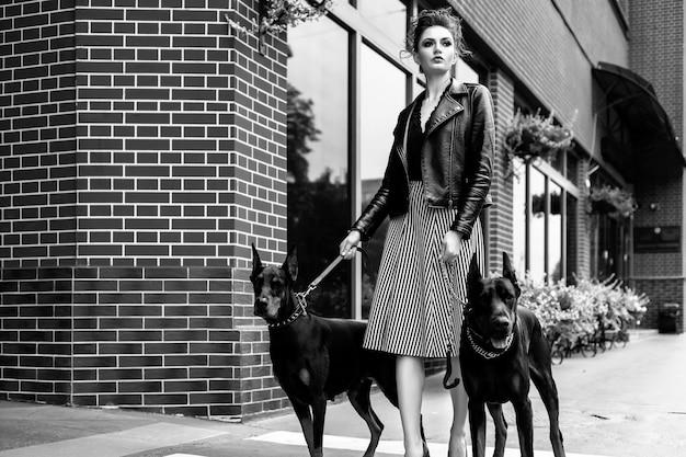 Una niña camina por la calle de la ciudad a lo largo del edificio con dos dobermans con una correa Foto Premium