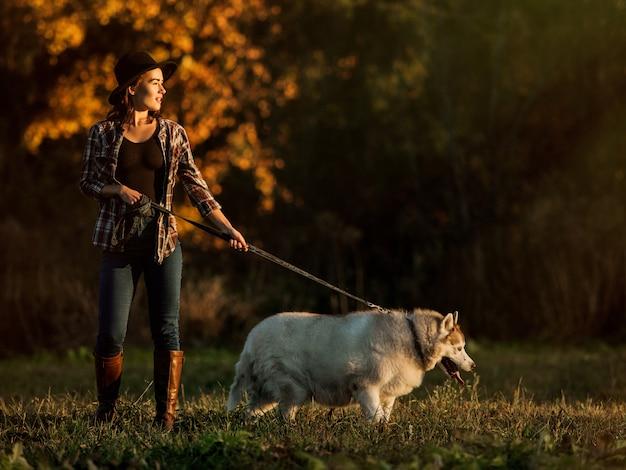 Niña camina con husky Foto gratis