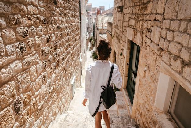 Niña caminando por antiguas calles estrechas en un hermoso día de verano Foto gratis
