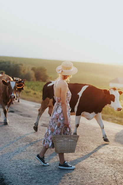 Niña en campo de granja con vacas en blanco y negro Foto Premium