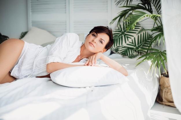 Niña cansada se relaja en la cama en el hotel solo Foto gratis