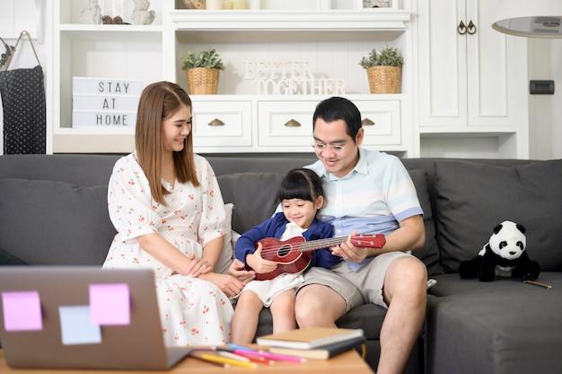 Niña cantando y tocando la guitarra con su familia mientras está sentada en el sofá en casa Foto Premium