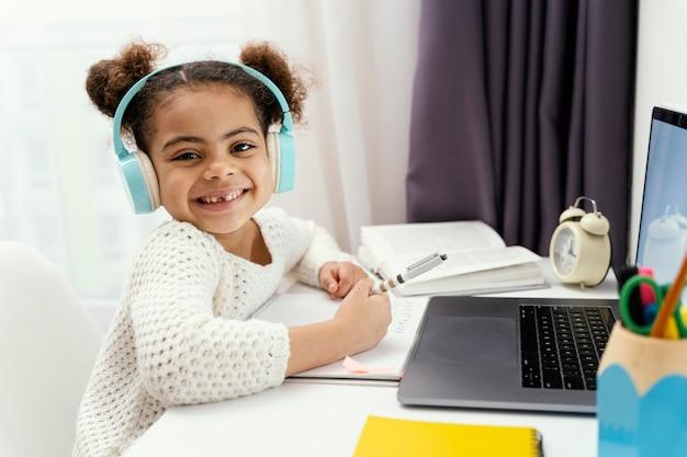Niña en casa durante la escuela en línea con laptop y auriculares Foto gratis