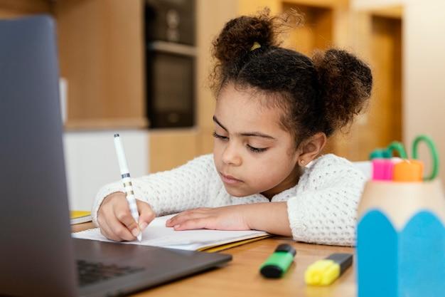 Niña en casa durante la escuela en línea con laptop Foto gratis