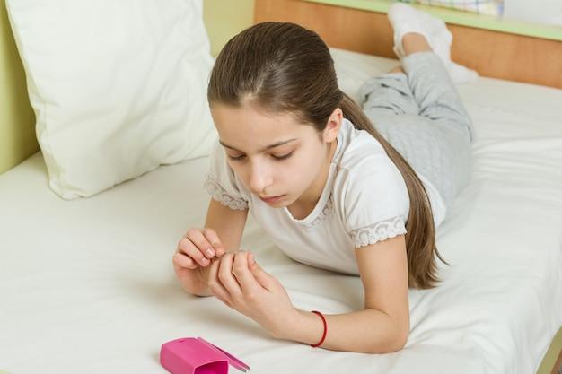 La niña se clava las uñas con accesorios de manicura Foto Premium