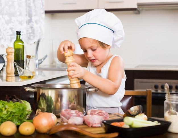Niña cocinando con carne Foto gratis