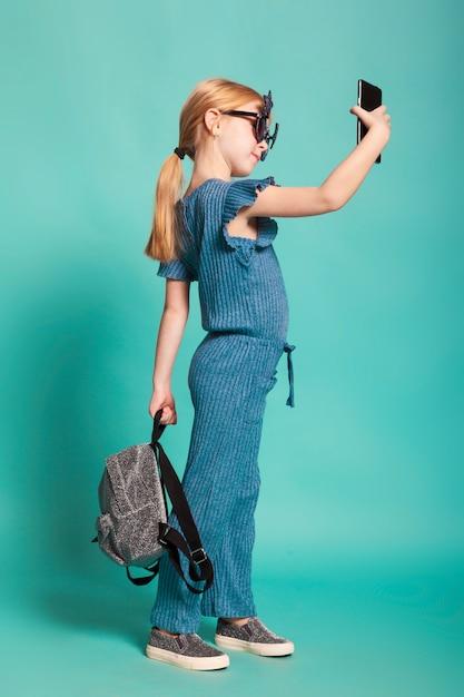 Niña con una cola en ropa elegante y gafas de sol Foto Premium