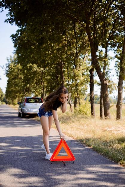 Niña colocando señal de stop triángulo rojo después del aplastamiento del coche en el campo Foto Premium