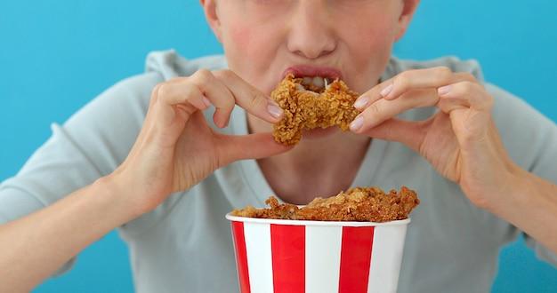 Niña comiendo alitas de pollo Foto Premium