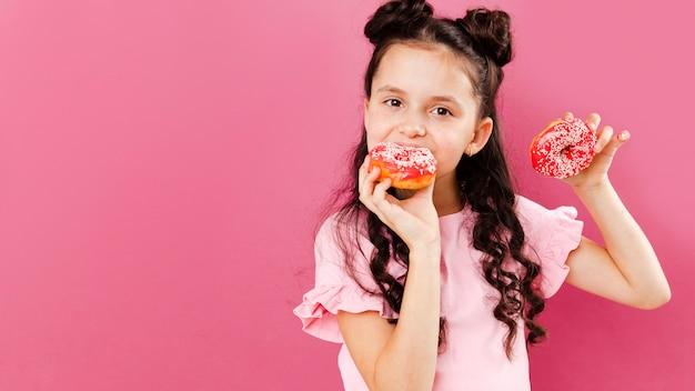 Niña comiendo deliciosas donas con espacio de copia Foto gratis