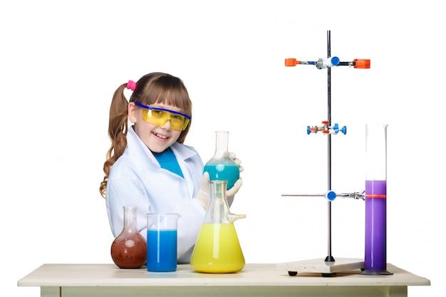 Niña como químico haciendo experimento con fluido químico en el laboratorio Foto gratis