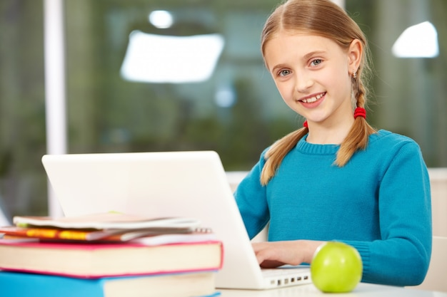 Niña con jersey azul estudiando con su portátil | Descargar Fotos ...