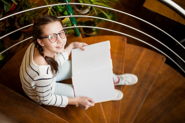 La niña en copas con un libro en sus manos. Foto Premium