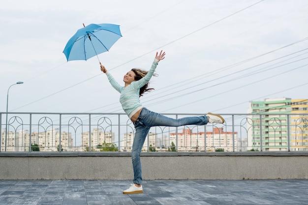 Niña corre detrás de un paraguas Foto Premium