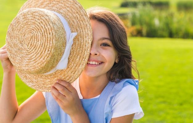 Niña cubriéndose los ojos con un sombrero Foto gratis