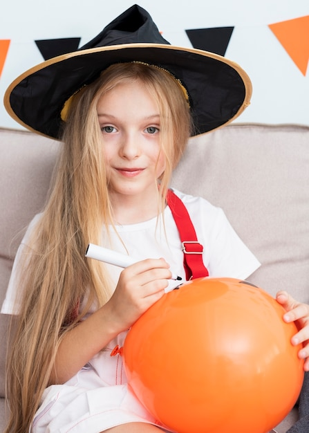 Niña dibujando un globo de halloween Foto gratis