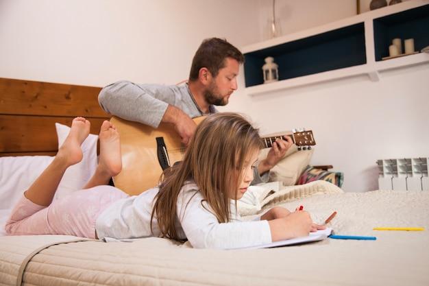 Niña dibujando mientras su padre toca la guitarra Foto gratis