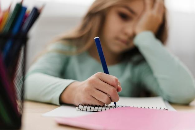Niña con dolor de cabeza mientras hace sus deberes Foto gratis