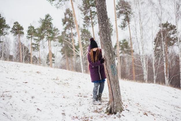 Niña se encuentra cerca de un árbol, paseo de invierno en el bosque o parque Foto Premium