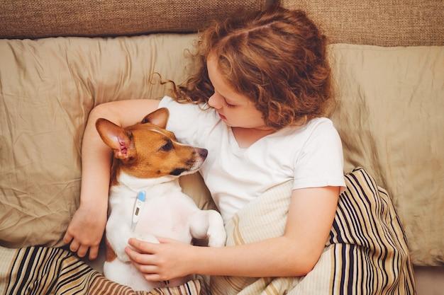Niña enferma y cachorro debajo de la colcha Foto Premium