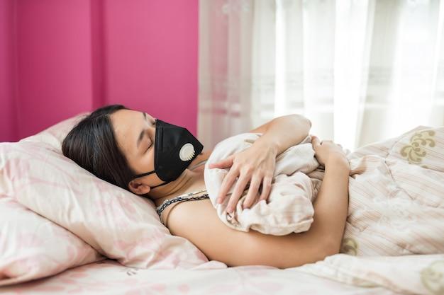 Niña enferma con máscara de sueño en cama Foto Premium
