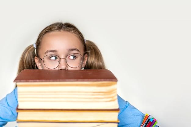 Niña de la escuela estresada, cansada de aprender con dificultad con los libros en los exámenes, preparación de exámenes, niña de la escuela secundaria abrumada y agotada, con estudios difíciles o demasiada tarea Foto Premium