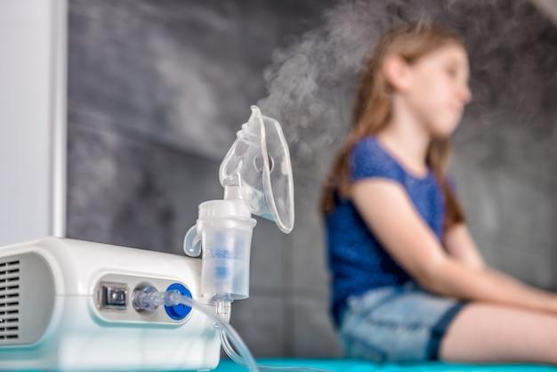 Niña esperando tratamiento de inhalación médica con un nebulizador Foto Premium