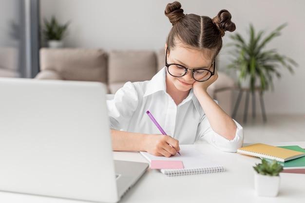 Niña estudiando en la computadora portátil Foto Premium