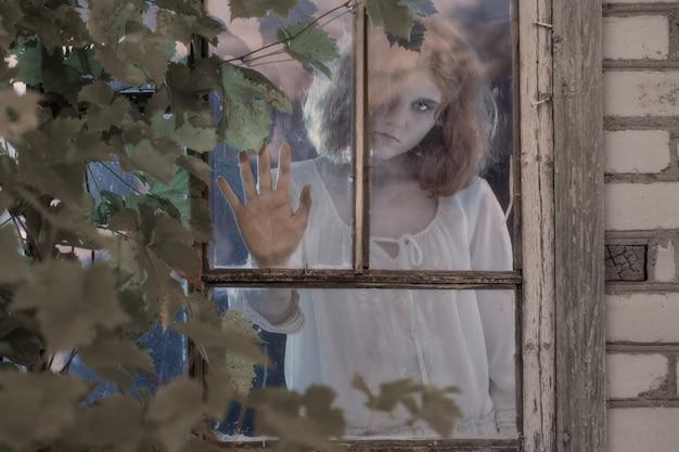 Niña fantasma en la ventana vieja Foto Premium