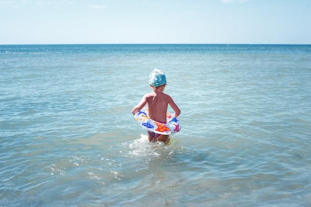 Niña feliz se baña en agua azul en un círculo inflable Foto Premium